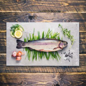 A whole rainbow trout on a board with herbs and assorted accompaniments