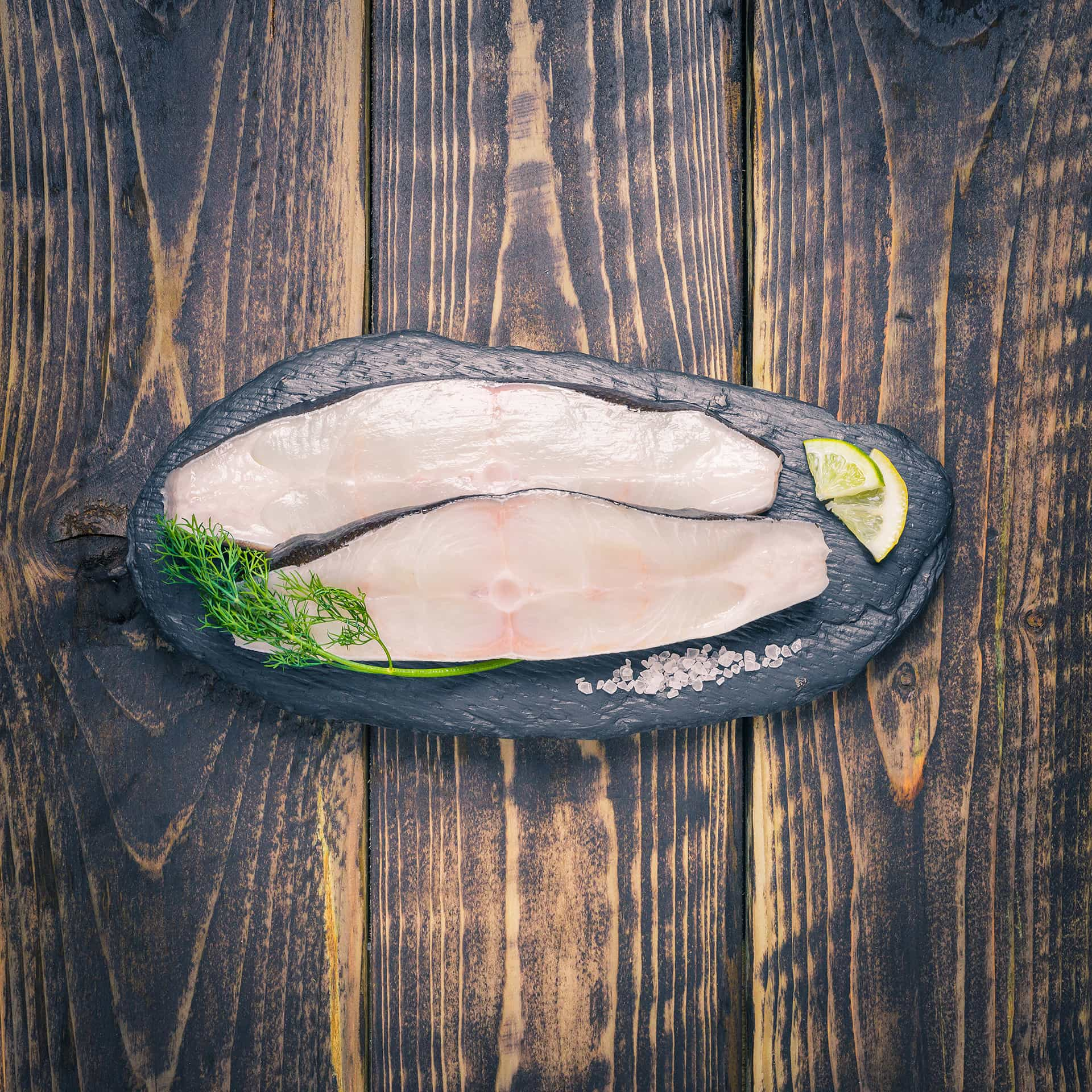 Halibut steaks on a slate background