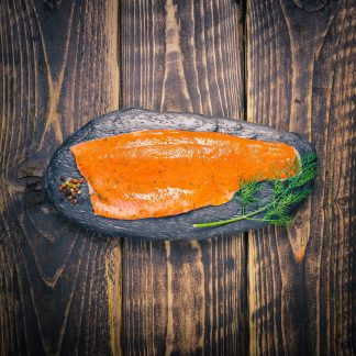 Orange and dill trout fillet on a slate background