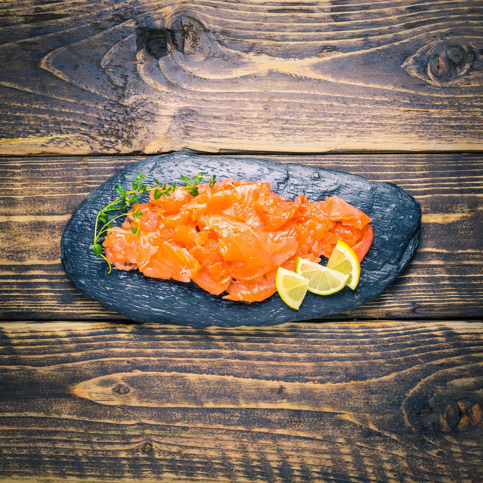 Smoked salmon trimmings on a slate background