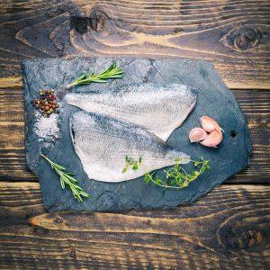 sea bream fillets on a slate background