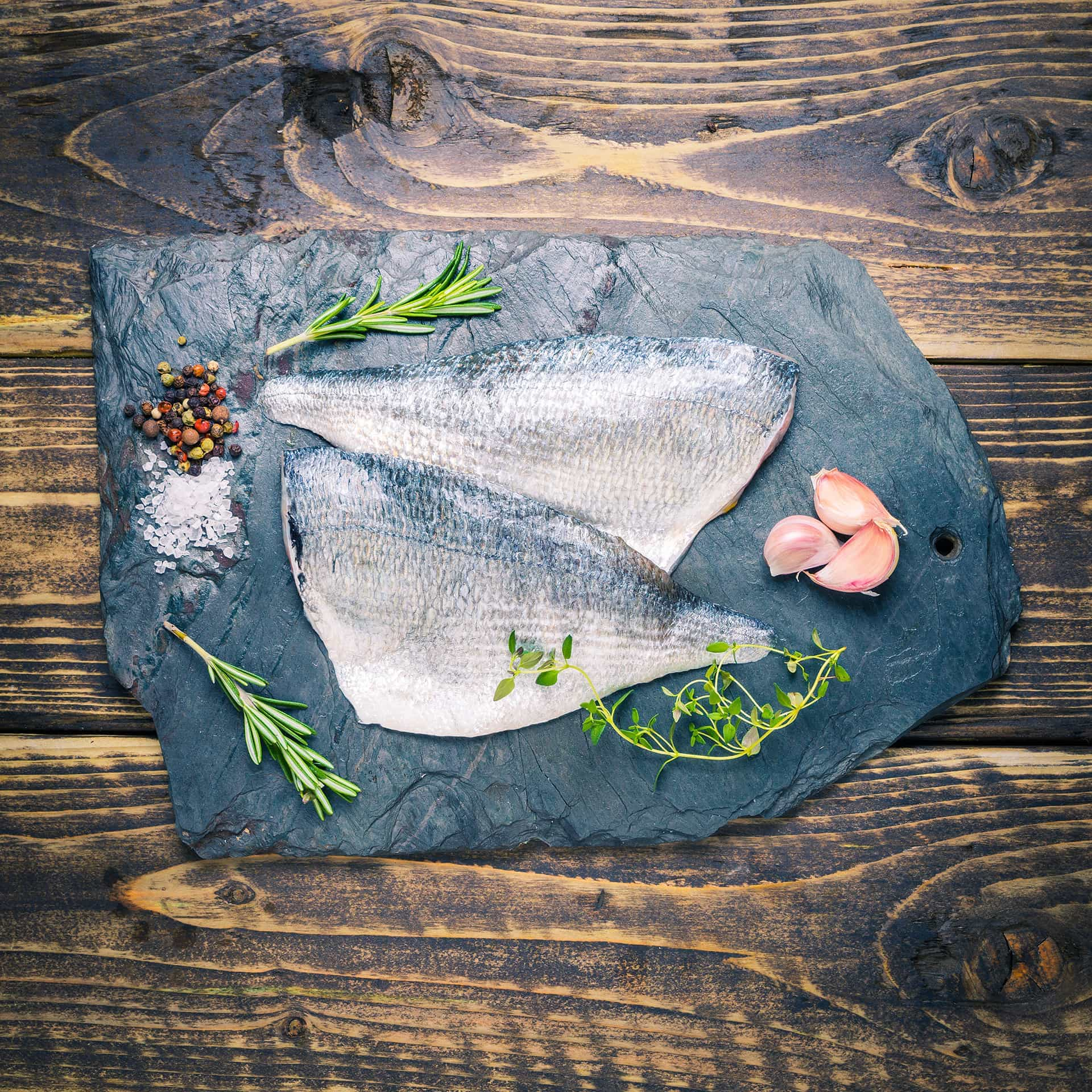 Sea bream fillets on a slate background