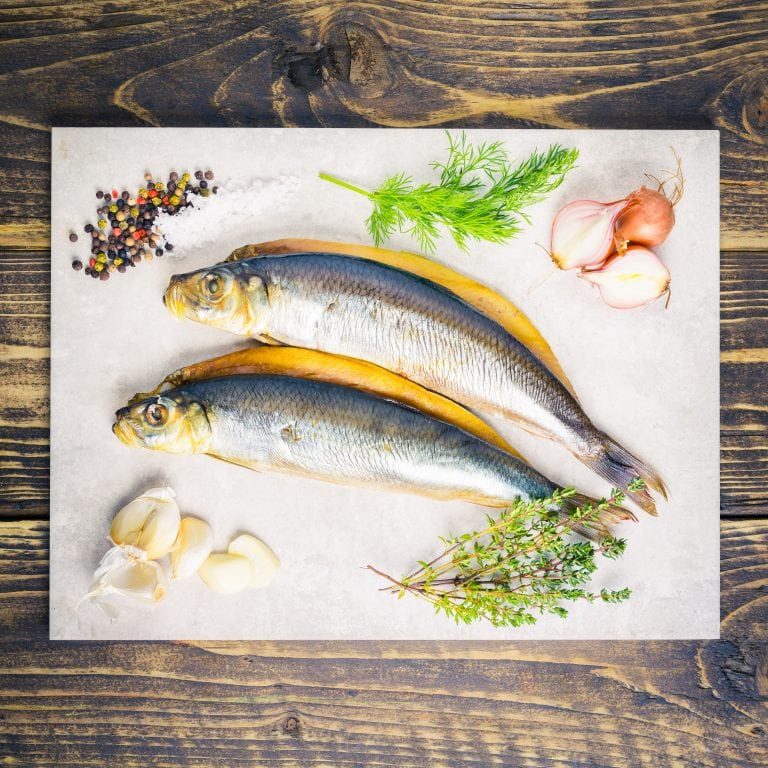 two kippers on a board with shallots, herbs and seasoning