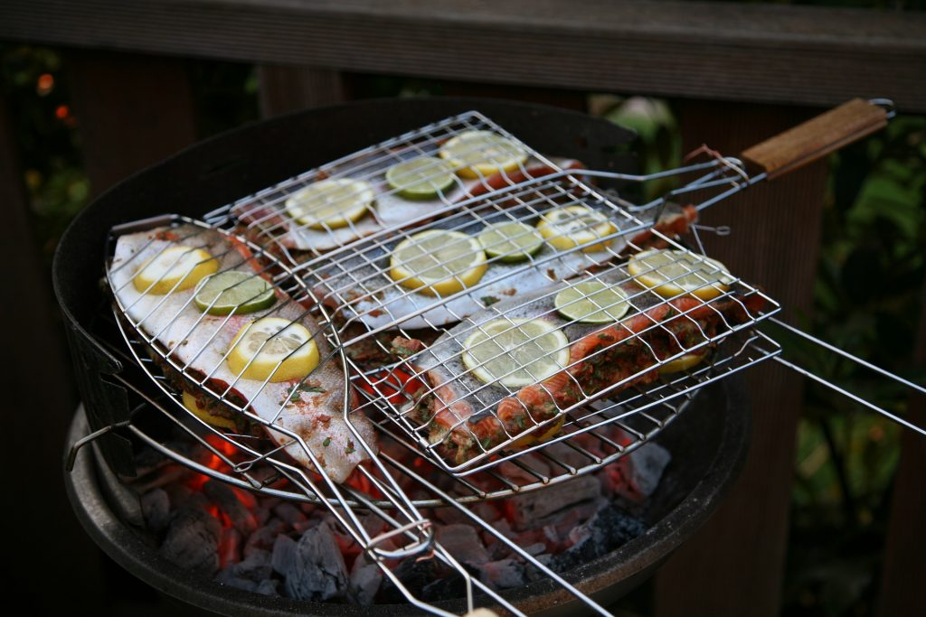 Fish being grilled in fish baskets over hot coals